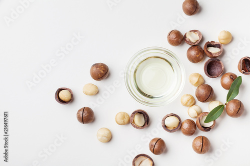 Organic macadamia oil and heap of nuts on white table top view.