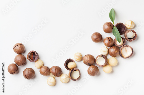 Heap of macadamia nuts on white table top view.