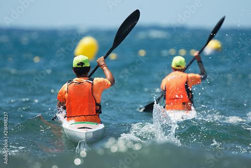 Paddlers race their ocean kayak surf skis through breaking