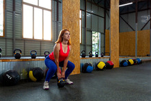 A Young Red-haired Woman In A Pink Top And Purple Leggings Doing Sit-ups With A Weight In The Sports Gym. Technique Of Squats With Weight