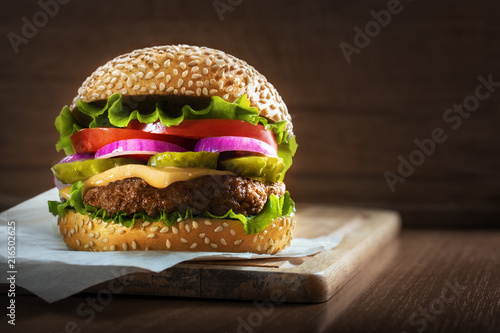 Tasty grilled delicious burger with lettuce, cheese, onion and tomato on a rustic wooden plank on a dark brown background