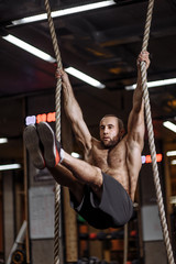 Handsome muscular young man hanging on two ropes. close up side view photo. sport and fitness concapt.professional sport