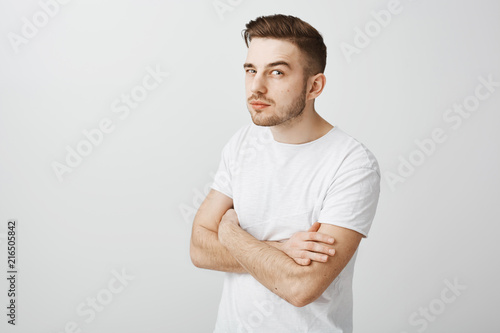 Upper-angle shot of suspicious handsome and funny european guy with beard holdin Canvas Print