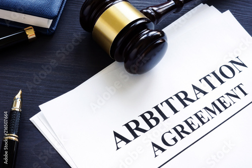 Photo Arbitration agreement and gavel on a desk.