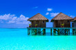 canvas print picture - Water villas on wooden pier in turquoise ocean on the white sand beach