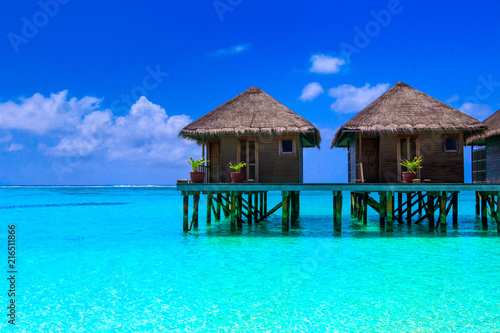 Spoed Foto op Canvas Donkerblauw Water villas on wooden pier in turquoise ocean on the white sand beach