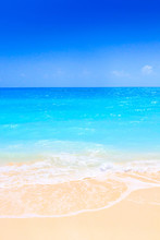Lonely Sandy Beach With Turquoise Ocean And Blue Sky