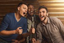 Happy Friends Singing Karaoke Together In Bar