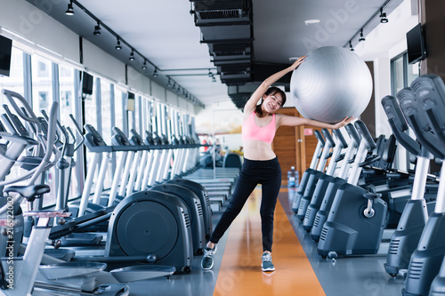 Woman exercise workout in gym fitness breaking relax.Women raise the ball happily in the gym.