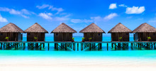 Water Villas On Wooden Pier In Turquoise Ocean On The White Sand Beach