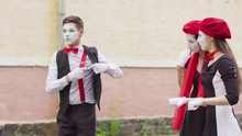 Three Funny Mimes Play Joking Scenes On City Street