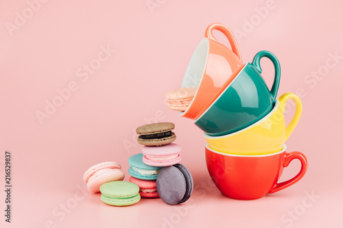Colorful stack of cups for latte coffee with sweet french macaroons cake in a vintage pastel colored tone on pink background with copy space.