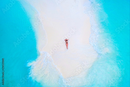 Beautiful woman tans on sandbank surrounded by turquoise ocean from above