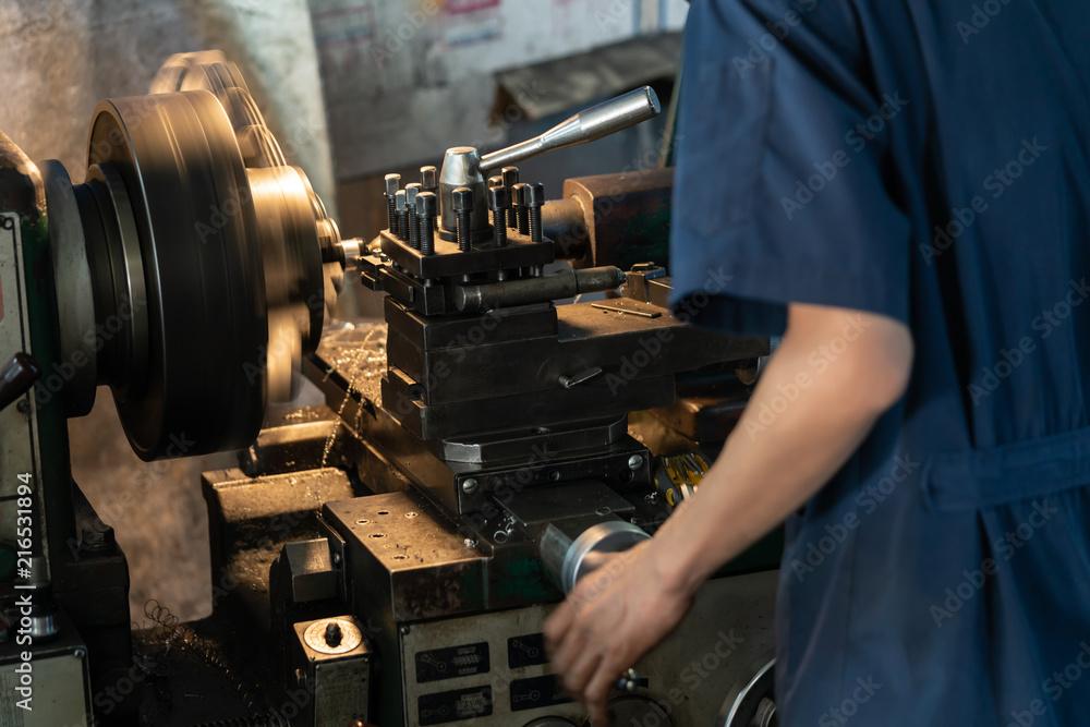 Fototapeta Professional machinist : man operating lathe grinding machine - metalworking industry concept. Mechanical Engineering control lathe machine in factory.