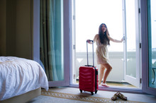 Lifestyle Portrait Of Young Happy And Beautiful Asian Korean Tourist Woman With Suitcase Arriving To Luxury Hotel Room Opening Balcony Windows
