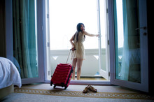 Lifestyle Portrait Of Young Happy And Beautiful Asian Chinese Tourist Woman With Suitcase Arriving To Luxury Hotel Room Opening Balcony Windows