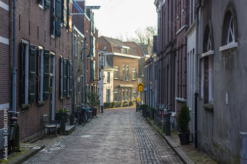 Gouda, South Holland/The Netherlands - March 31 2018: early morning sunrise in the city center of Gouda seen from a abandoned small side street