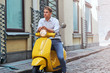Portrait of a pensive stylish guy dressed in a in a white shirt and jeans sitting on yellow classic italian scooter on an old Europe street.