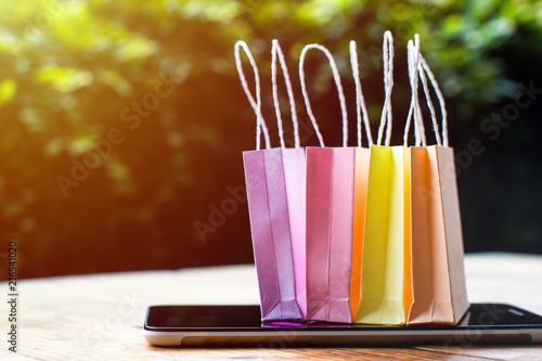Photo  Online shopping, E-commerce, fast and easy trading concept : Colorful mini shopping  bag, Paper bag on tablet depicts customers order things from retailer sites via the internet