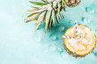 canvas print picture - Summer refreshment drink concept, tropical pineapple cocktail or juice in pineapple with ice, light blue concrete background copy space