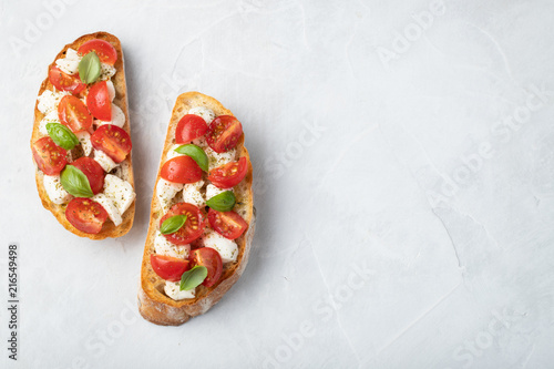Photo Bruschetta with tomatoes, mozzarella cheese and basil on a light background