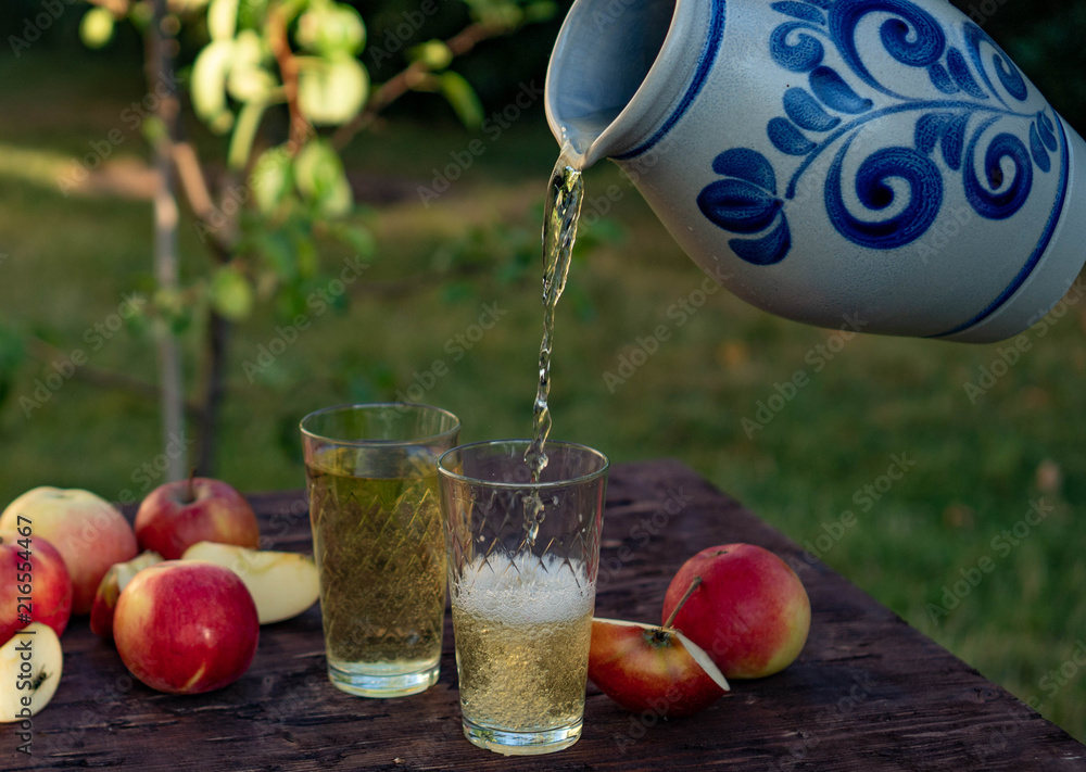 Fototapety, obrazy: a man's hand pours Traditional apple wine in a refilled glass in the city of Frankfurt. A jug of wine on an old wooden table in the garden, around it apples