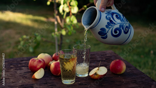 Foto a man's hand pours Traditional apple wine in a refilled glass in the city of Frankfurt