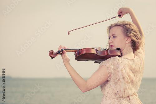 Woman playing violin on violin near beach