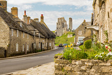 Corfe Castle Ruins In Dorset Seen On A Sunny Summer Day With Traditional Portland Stone Cottages Lining The Road In The Foreground