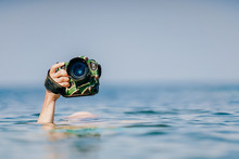 Unrecognizable Male Hand Holding Expensive Professional Photocamera In Waterproof Military Case Above Water In Ocean.  Odd Photographer Working In Extreme Dangerous Conditions. Safety And Protection.