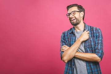 Portrait of a handsome casual man who laughs, standing and laughing over pink background