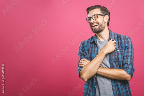 Obraz Portrait of a handsome casual man who laughs, standing and laughing over pink background - fototapety do salonu