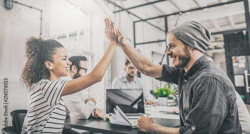 Photo  Happy business people team giving high five in office.