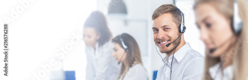 Call center worker accompanied by his team. Fototapeta