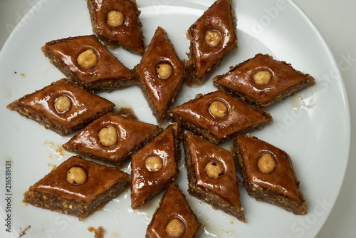 Traditional Azerbaijan dessert baklava with walnuts and cardamom on white plate. Homemade baklava with nuts and honey.