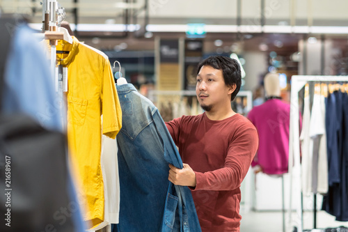 Smart Asian Man With Beard Choosing Clothes In Clothing Store At Shopping Center Compare The Differences Between Shirts Fashion Style And Consumerism Concept Buy This Stock Photo And Explore Similar Images