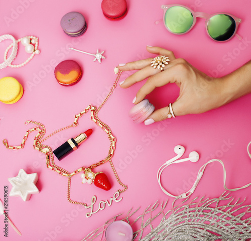 woman hands holding macaroons with lot of girl stuff on pink bac