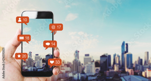 Photo  Hand holding mobile smart phone, with notification icons and city background
