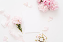 Elegant Feminine Wedding Or Birthday Flat Lay Composition With Pink Peonies Floral Bouquet, Silk Ribbon And Candle Blank Paper Card, Mockup, Invitations. Flatlay, Top View.