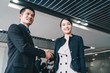 Businessman and Businesswoman shaking hands and discussion with colleague in meeting room or conference room and audience.