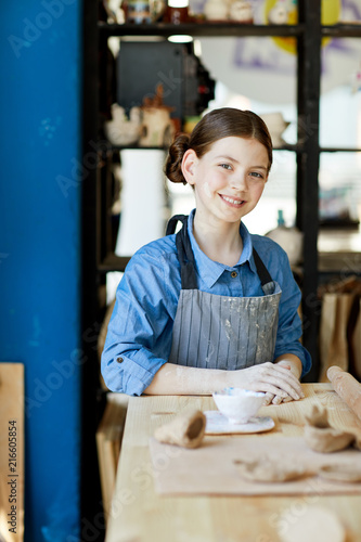 Foto op Plexiglas Bakkerij Cheerful schoolgirl in apron sitting by table in front of camera at lesson of clay craft