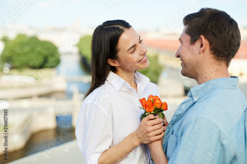 Happy young man in shirt giving pretty flowers to smiling beautiful happy young man in shirt giving pretty flowers to smiling beautiful girlfriend while they standing on mightylinksfo