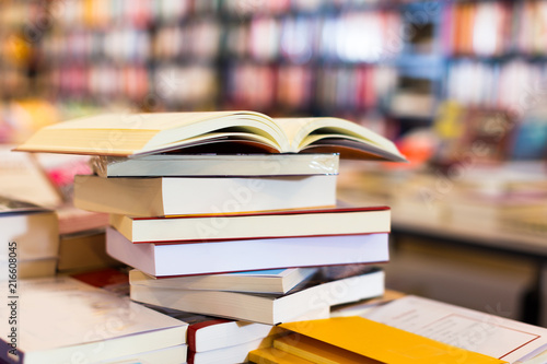 stack of books lying on table in bookstore Poster Mural XXL
