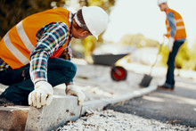 Worker With Gloves And In Helmet Arranging Curbs On The Street
