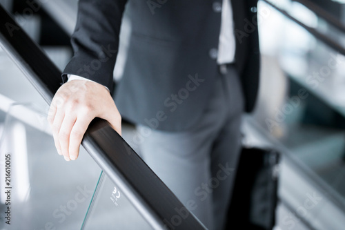 Fotografía Hand of young businessman on railings of escalator during motion downwards