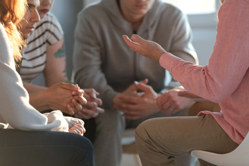 Close-up of a therapist gesticulating while talking to a group of listing teenagers during an educational self-acceptance and motivation meeting.