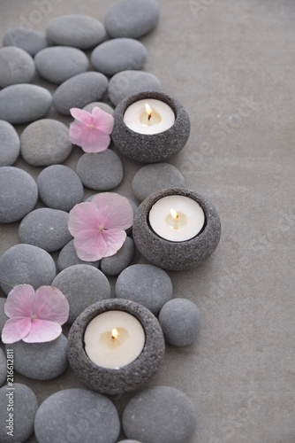 Pile of gray stones with three candle with Pink hydrangea petals and grey background