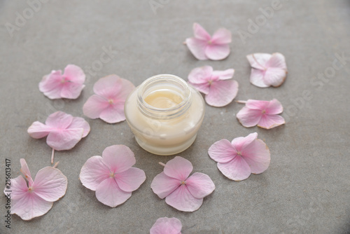 Poster Spa Many Pink hydrangea petals with cream in bottle, on gray background