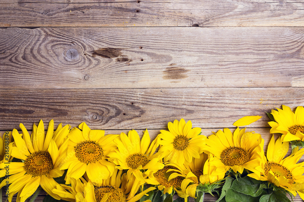 Yellow sunflowers on old wooden background. Copy space.