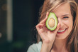 Leinwanddruck Bild - Smiling girl with an avocado